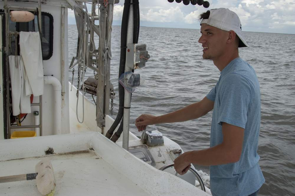 "Tommy Olander Jr. on Aug. 9 drives his family's shrimping boat in Vermillion Bay off the Louisiana coast near Jeanerette. Vermillion Bay, inland of the oxygen-deprived ""dead zone,"" was expected soon to be full of shrimp boats for the opening of the fall season as trawlers compete in the same inland waters for a shrinking pool of shrimp. (Photo by John Steppe)"